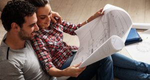 couple reading floor plan for new investment property