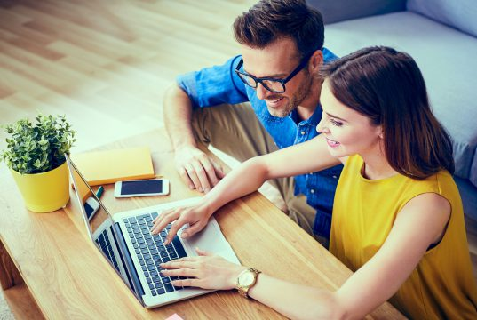 couple researching on laptop